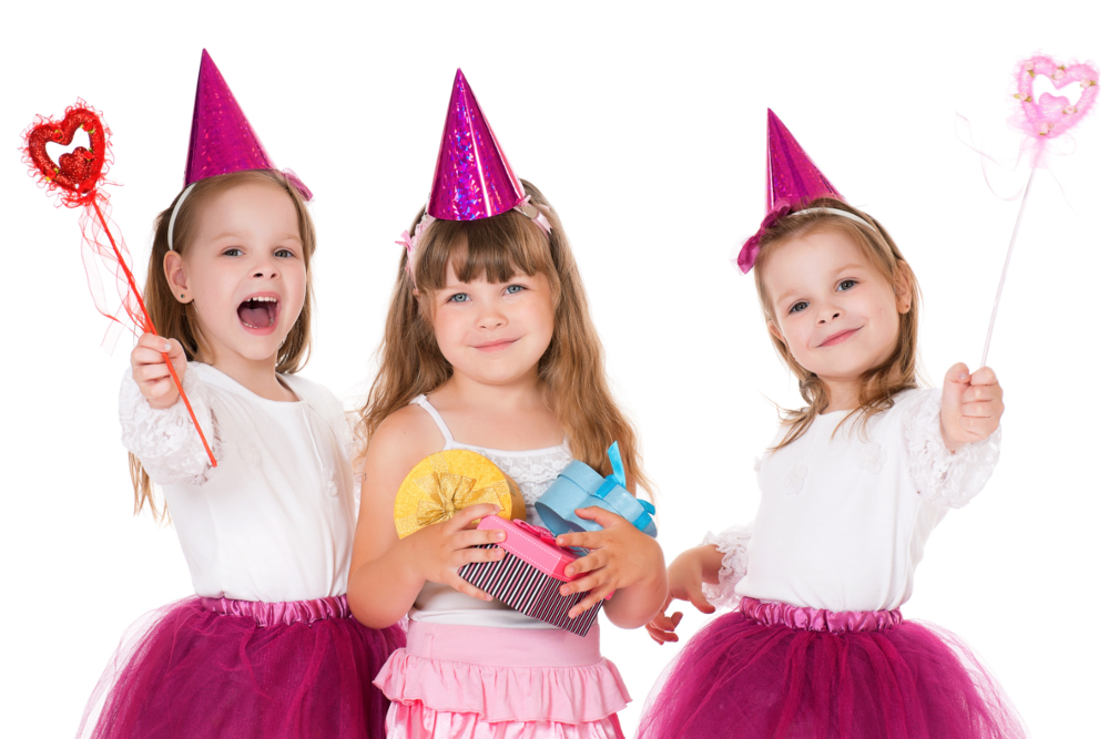 three young girls in party clothes with gifts and birthday hats