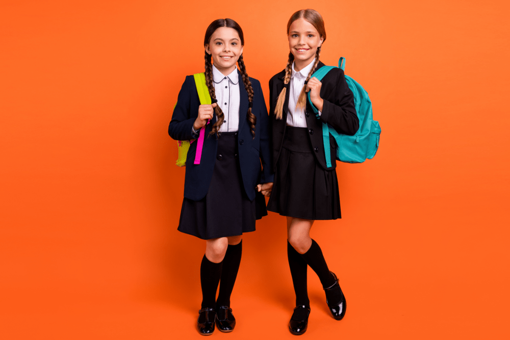 Girls with backpacks orange background